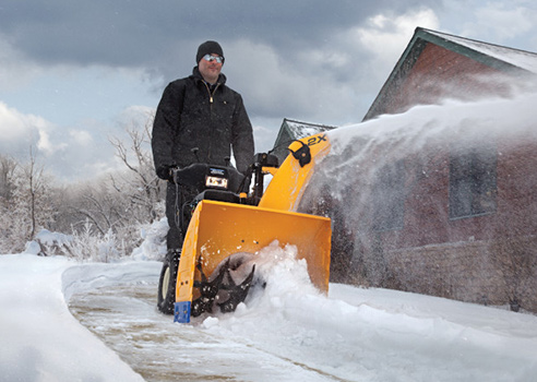 man pushing two stage snow blower