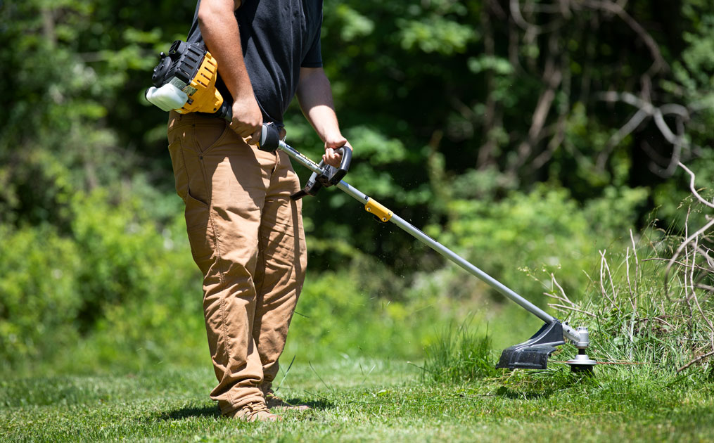 man trimming grass with weed wacker