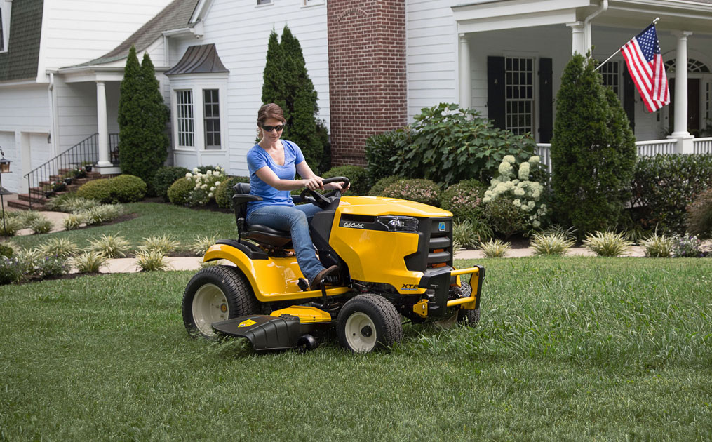 woman cutter her lawn with riding mower
