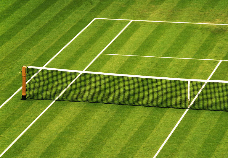 Beautifully mowed tennis court with net