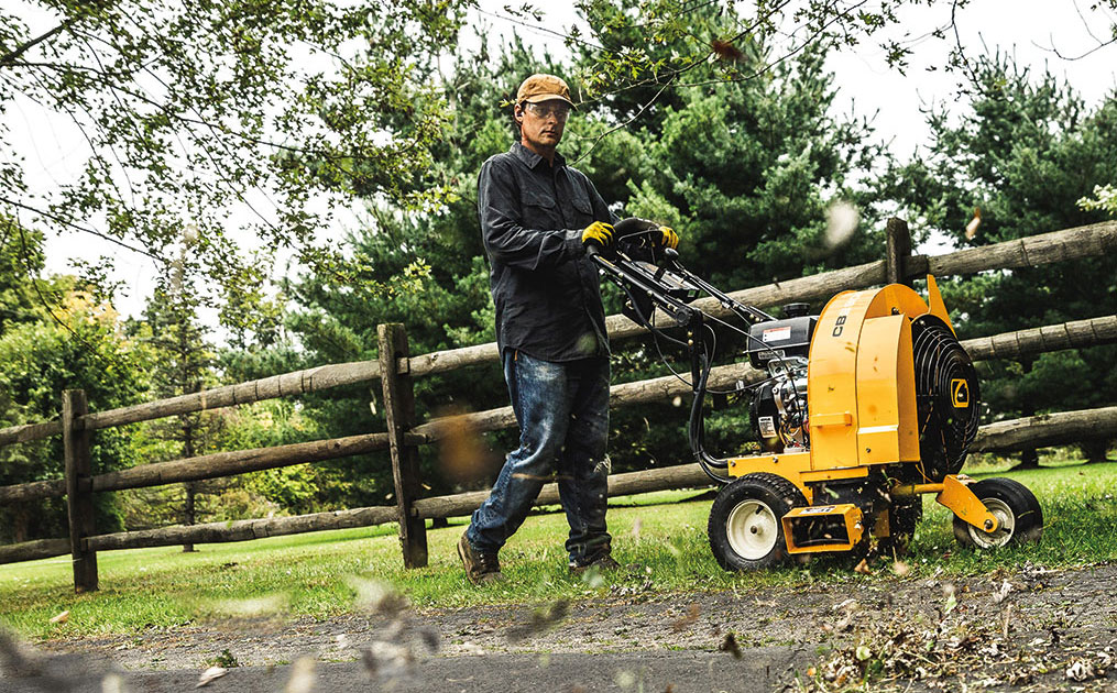 man using commercial blower to blow leaves off pavement