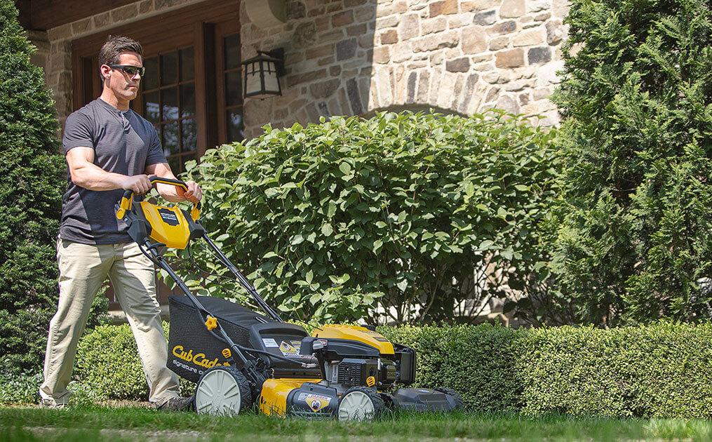 man cutting his lawn with walk-behind mower
