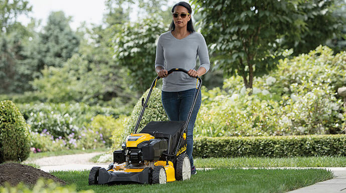 woman mowing with walk behind