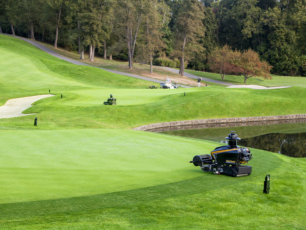 Man golfing and three commercial lawn mowers on golf course