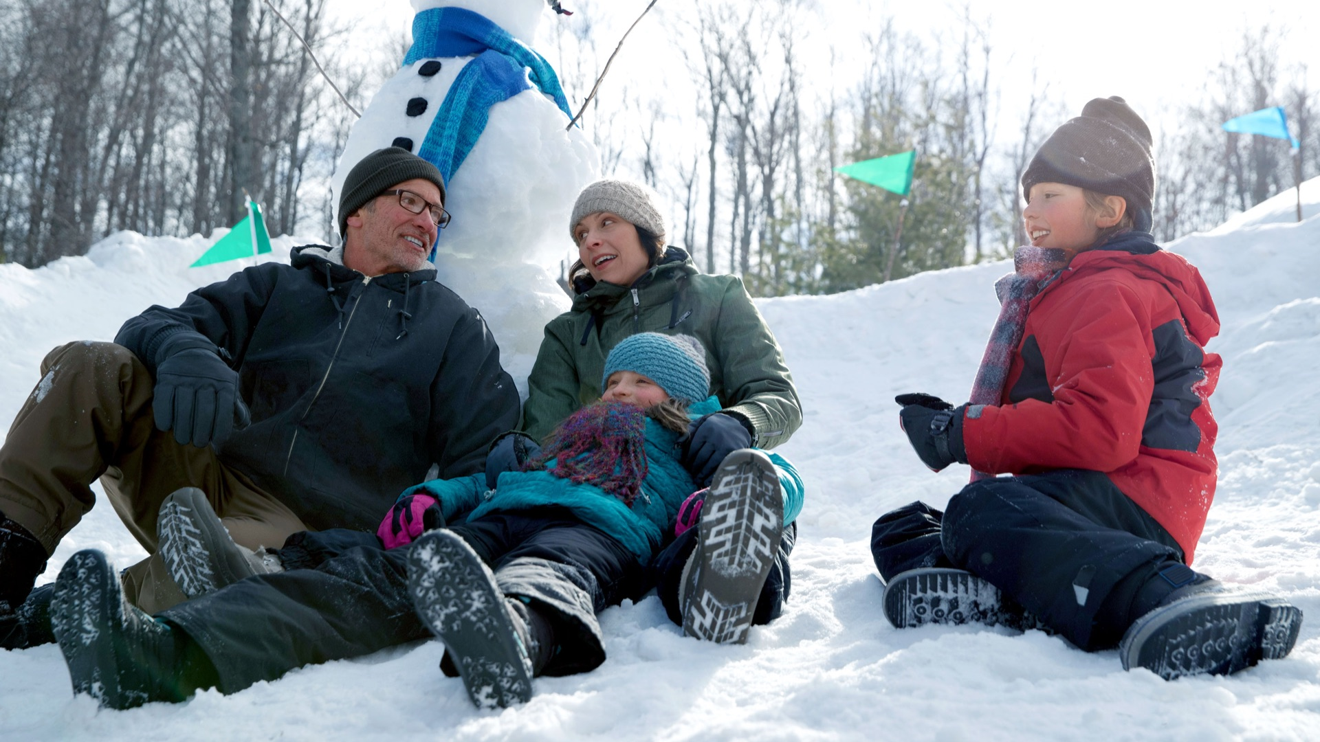 family sitting outdoors sitting in snow with snowman in background