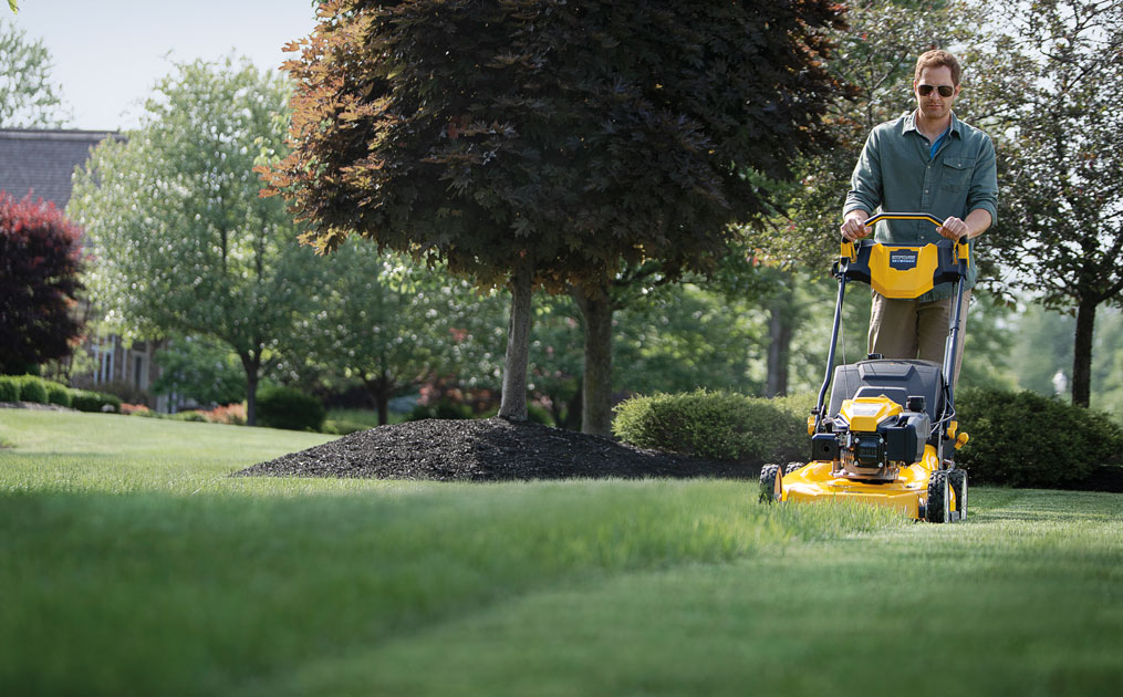 man cutting his lawn with walk-behind mower