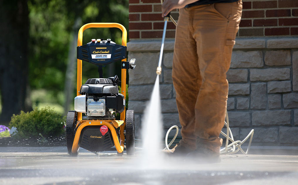 man using power washer on driveway