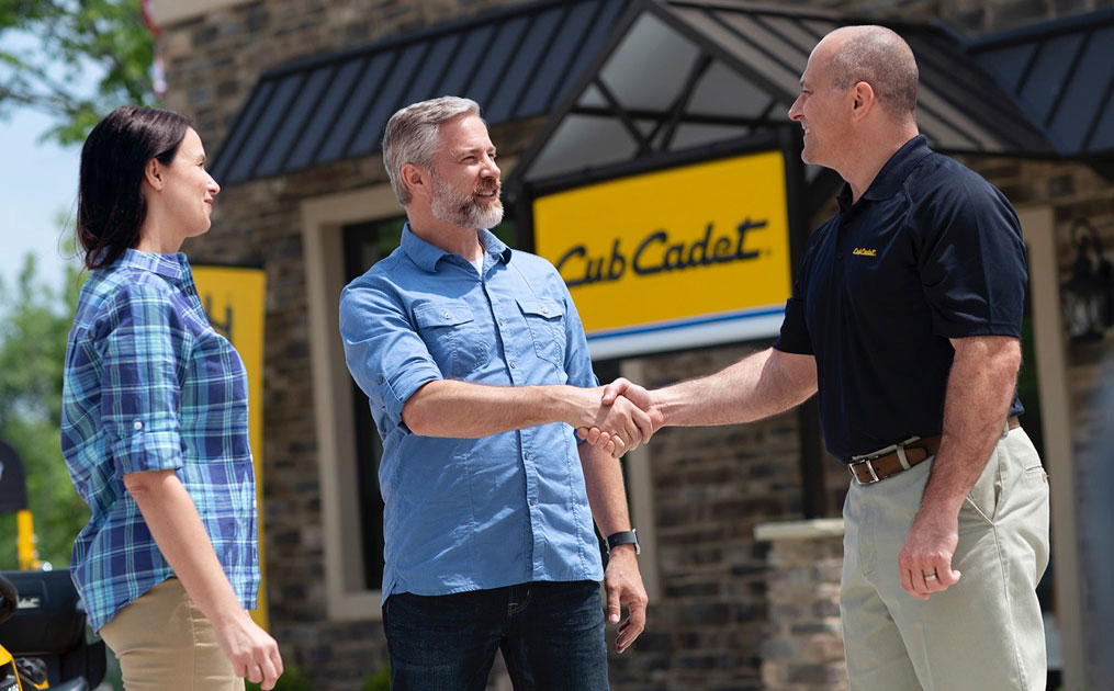 man shaking hands with salesman in front of store building