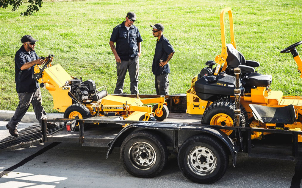 Three men loading commercial lawn mowers on a trailer