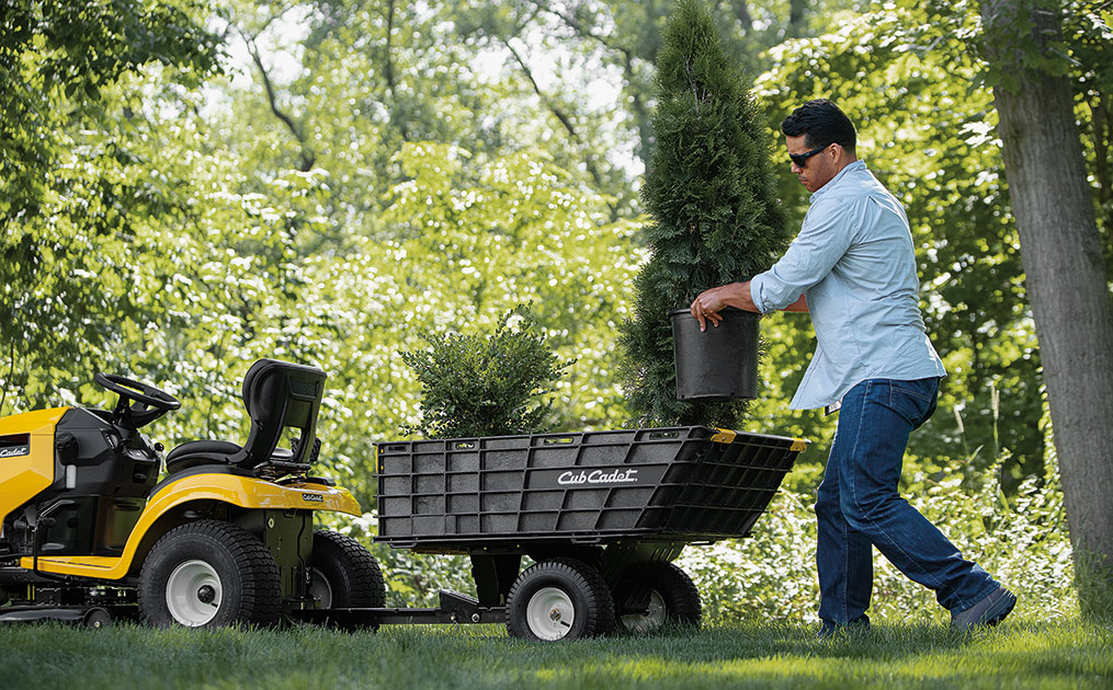Man putting a garden pot into a hauler cart attached to the back of a lawn tractor