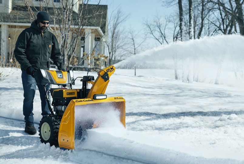 Man using cub cadet two stage snow blower to clear drive