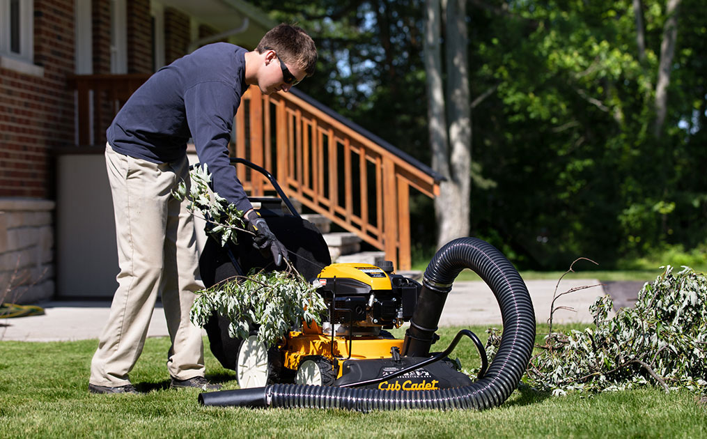 Man putting branches into Cub Cadet Shredder vacuum
