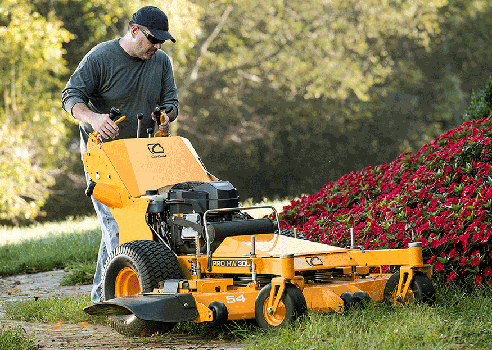 man cutting around flower bed with commercial walk-behind mower