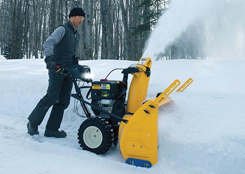 man pushing three stage snow blower