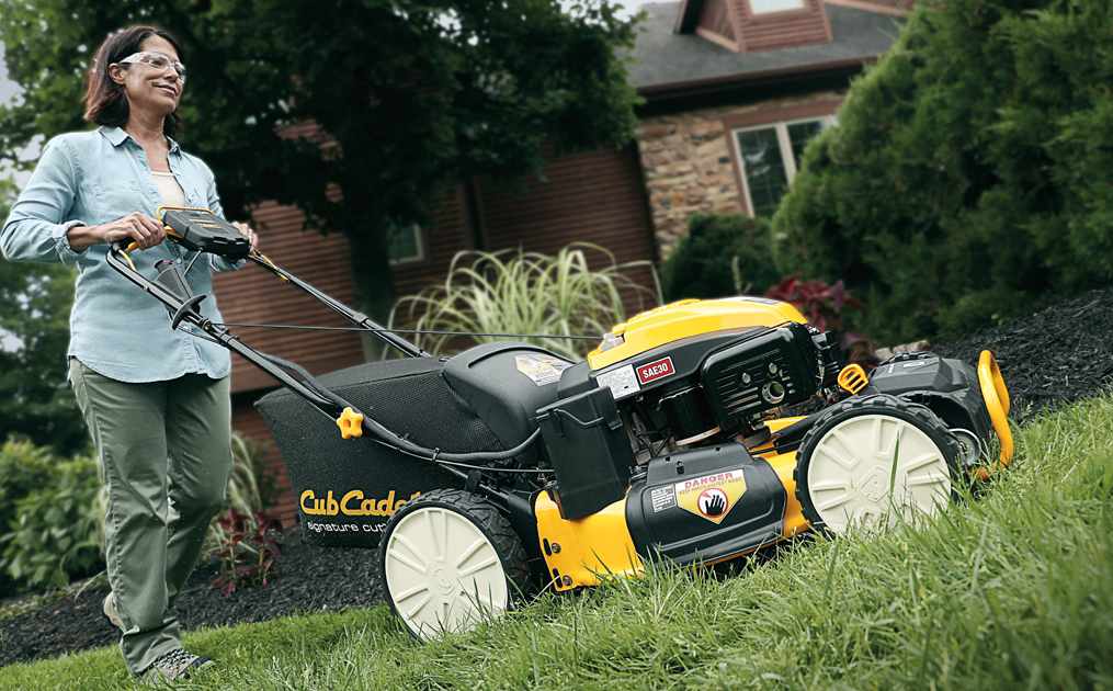 Woman cutting grass with walk behind mower