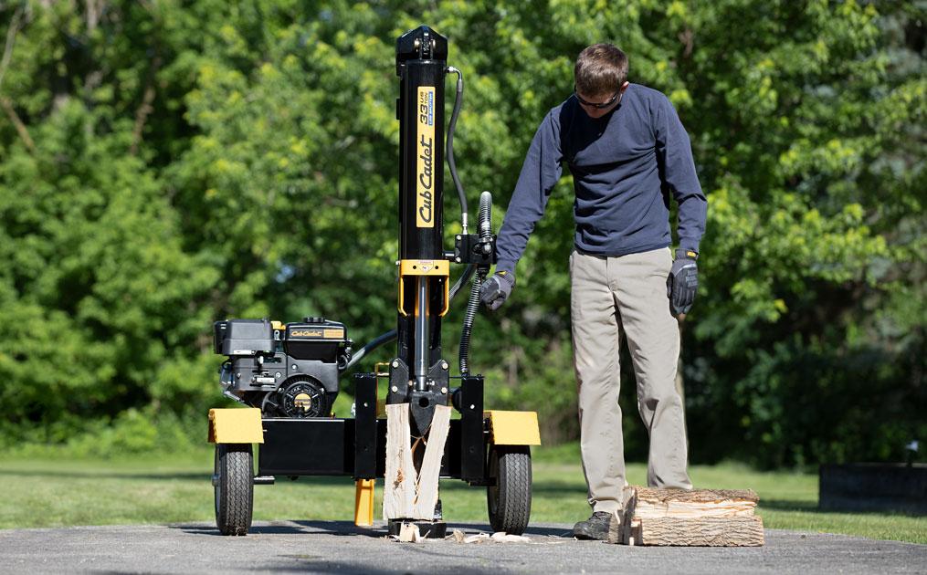 man using log splitter on a piece of wood