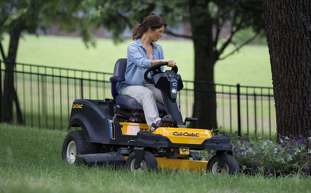 Woman on zero-turn lawn mower cutting grass