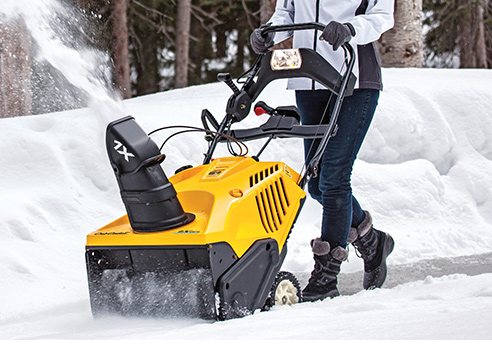 woman pushing single stage snow blower