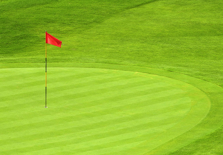 Red flag in a hole on a golf course